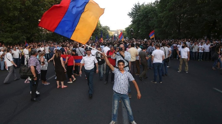 In this photo taken late Monday, June  22, 2015, an Armenian protester waves a national flag during a protest rally in the Armenian capital of Yerevan against a hike in electricity prices. Police in the Armenian capital have dispersed several hundred demonstrators who blocked a central avenue as part of their protest. About 5,000 demonstrators marched Monday to the presidential headquarters, but were stopped by phalanxes of riot police backed by water cannons. (Hrant Khachatryan/PAN Photo via AP)