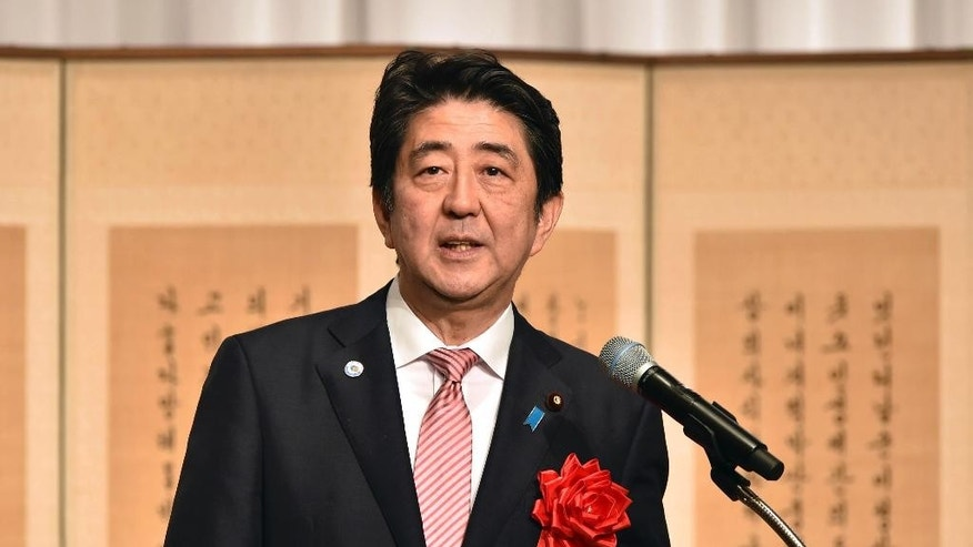 Japanese Prime Minister Shinzo Abe delivers a speech at a ceremony to mark the 50th anniversary of normalizing relations between Japan and South Korea, hosted by South Korean Embassy in Tokyo Monday, June 22, 2015. South Korean Foreign Minister Yun Byung-se attended the ceremony. (Yoshikazu Tsuno/Pool Photo via AP)