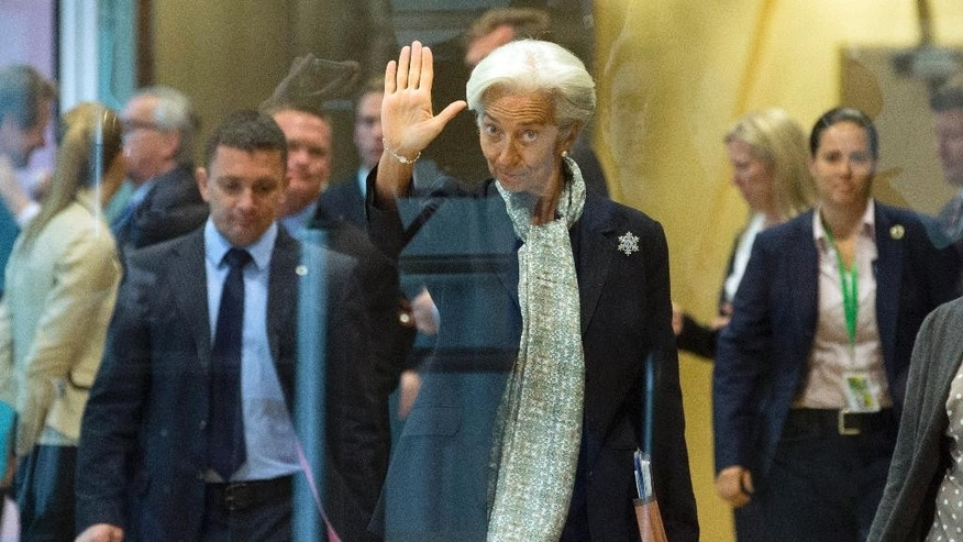 Managing Director of the International Monetary Fund Christine Lagarde, center, waves as she arrives for a meeting at EU headquarters ahead of an EU Summit in Brussels on Monday, June 22, 2015. Heads of state in the eurogroup will meet in Brussels on Monday for a special summit to discuss the financial crisis with Greece. (Olivier Hoslet/Pool Photo via AP)