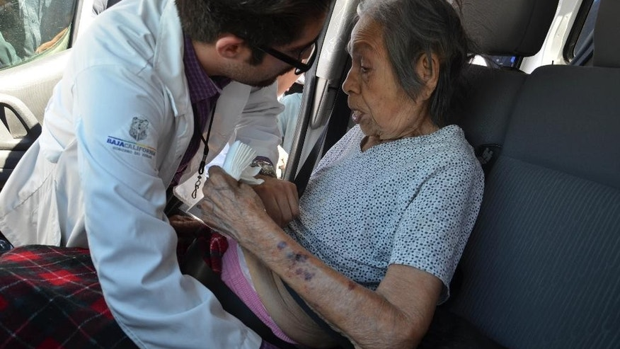 A paramedic attends an elderly woman after evacuating her from a nursing home that caught fire in Mexicali, Mexico, Tuesday, June 23, 2015. The fire killed more than a dozen elderly residents at the home, and the cause of the blaze was being investigated by the state prosecutors' office, according to Mexicali Mayor Jaime Diaz Ochoa. (AP Photo/Cristian Torres)
