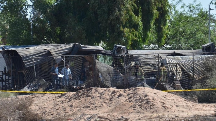 Forensics work among the rubble of a nursing home after it caught fire in Mexicali, Mexico, Tuesday, June 23, 2015. The fire killed more than a dozen elderly residents at the home, and the cause of the blaze was being investigated by the state prosecutors' office, according to Mexicali Mayor Jaime Diaz Ochoa. (AP Photo/Cristian Torres)
