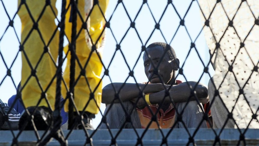 A migrant sits on the deck of the German ship Holstein, in the port of Salerno, southern Italy, after being rescued at sea, Monday, June 22, 2015. The Holstein rescued more than 500 migrants in various operations over the last days. (AP Photo/Francesco Pecoraro)