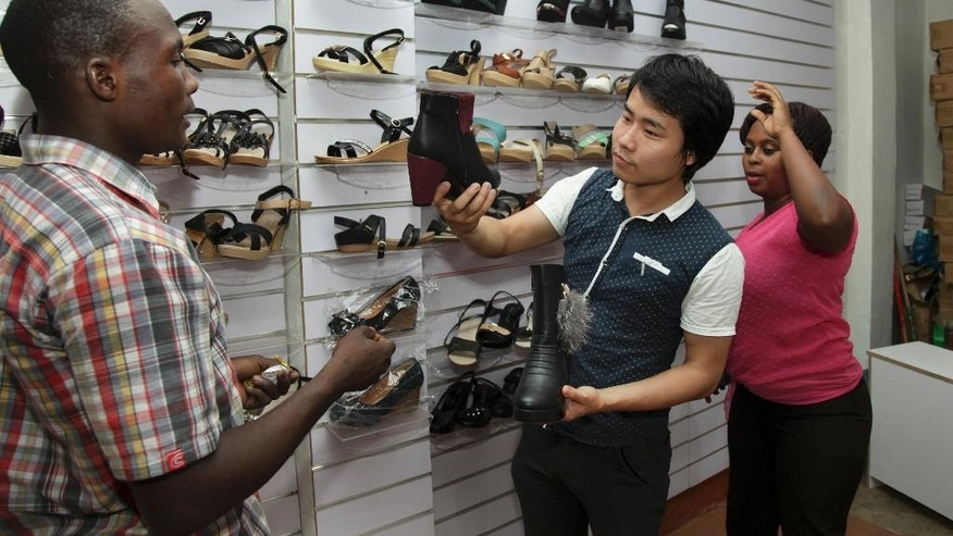 In this photo taken Monday, June 8, 2015, Chinese national Wei Kun, center, and his sales executive Allen Tushabe, right, sell a pair of shoes made in China to a customer at their shop in Kampala, Uganda. Over the past 10 years, Chinese industrial giants have invested billions across Africa, and there has been an accompanying explosion of retailers opening small shops from Senegal in the west to Algeria in the north, Zimbabwe in the south and Uganda in the east. (AP Photo/Stephen Wandera)