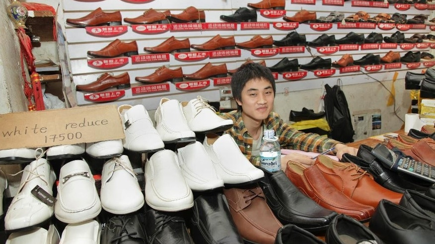 In this photo taken Monday, June 8, 2015, a Chinese shoe-seller, who declined to give his name, sits by his wares at a shoe shop in Kampala, Uganda. Over the past 10 years, Chinese industrial giants have invested billions across Africa, and there has been an accompanying explosion of retailers opening small shops from Senegal in the west to Algeria in the north, Zimbabwe in the south and Uganda in the east. (AP Photo/Stephen Wandera)