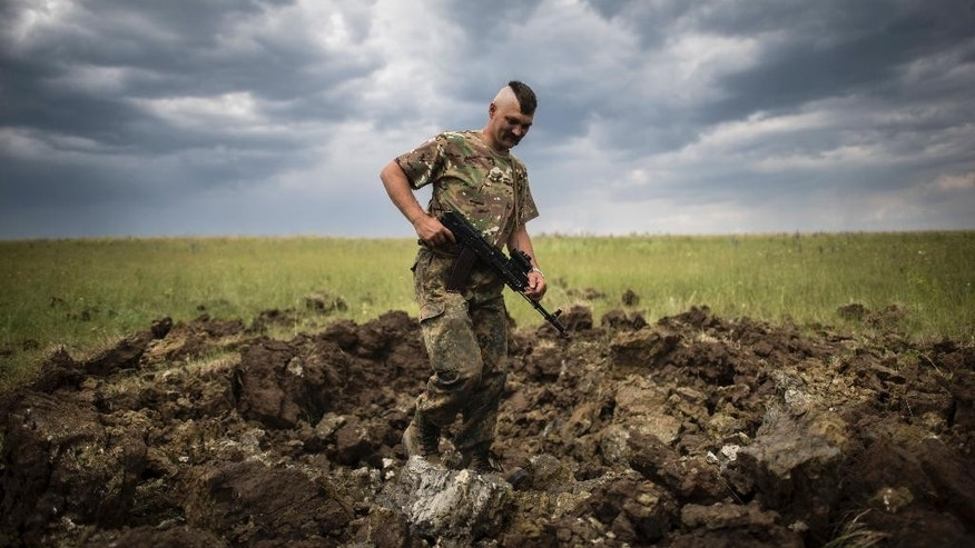 FILE - In this Monday, June 15, 2015 file photo, a Ukrainian serviceman investigates a crater left by a Grad rocket in the village of Toshkivka, Luhansk region, eastern Ukraine. (AP Photo/Evgeniy Maloletka, File)