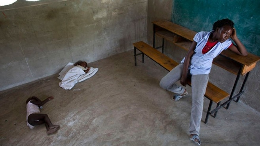 In this Thursday, June 18, 2015 photo, Milene Monime, 16, sits as her two-month-old son Jefferson Thezon, center, sleeps next to another person's child inside a school classroom where her family and others are staying after being deported the previous day from neighboring Dominican Republic, in the village of Fonbaya, Haiti. People began preparing Thursday for deportation from the Dominican Republic after failing to obtain legal residency as part of a government program to crack down on migrants, most of them from neighboring Haiti or of Haitian descent. (AP Photo/Rebecca Blackwell)