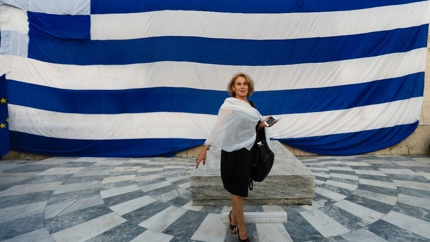 A pro-Euro demonstrator walks next to a giant Greek flag during a rally outside the Greek Parliament in Athens, Monday, June 22, 2015. Thousands of people gathered to show support for the country's future in the eurozone and the European Union. (AP Photo/Daniel Ochoa de Olza)