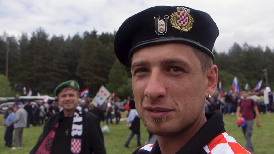 "CORRECTS DATE IN INSTRUCTIONS - In this May 16, 2015 photo, a man from Croatia wearing WWII Croatian ""Ustasha"" insignia attends a memorial to the thousands of victims of the mass killings by Yugoslav communists, in Bleiburg, Austria. At the time when most of Europe marked the 70th anniversary of liberation from the Nazi occupiers, thousands of right-wing Croats were out in a field in southern Austria honoring the WWII Ustasha state that was responsible for sending tens of thousands of Serbs, Gypsies and Jews to their death in concentration camps. (AP Photo/Darko Bandic)"