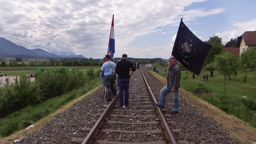 In this May 16, 2015 photo, men from Croatia stand on railway tracks as they attend a memorial  to the thousands of victims of the mass killings by Yugoslav communists, in Bleiburg, Austria. At the time when most of Europe marked the 70th anniversary of liberation from the Nazi occupiers, thousands of right-wing Croats were out in a field in southern Austria honoring the WWII Ustasha state that was responsible for sending tens of thousands of Serbs, Gypsies and Jews to their death in concentration camps. (AP Photo/Darko Bandic)