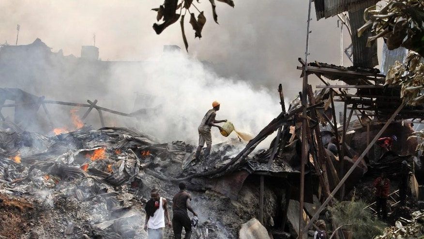 A man throws water on the smouldering remains of market stalls after an overnight fire in the Gikomba open-air market in Nairobi, Kenya Tuesday, June 23, 2015. Firefighters struggled for hours to contain the blaze which destroyed the market, which sells mainly secondhand clothes, as well as a number of surrounding residences, but no casualties were reported according to the Kenya National Disaster Operation Centre. (AP Photo/Khalil Senosi)