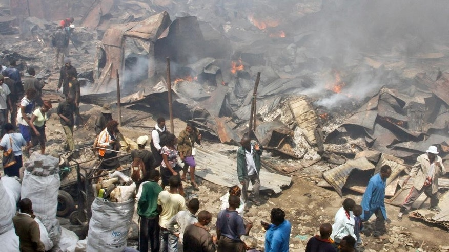 Residents look at the remains of market stalls after an overnight fire in the Gikomba open-air market in Nairobi, Kenya Tuesday, June 23, 2015. Firefighters struggled for hours to contain the blaze which destroyed the market, which sells mainly secondhand clothes, as well as a number of surrounding residences, but no casualties were reported according to the Kenya National Disaster Operation Centre. (AP Photo/Khalil Senosi)