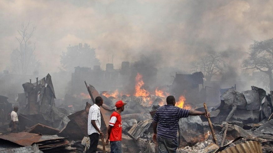 Residents watch the remains of market stalls after an overnight fire in the Gikomba open-air market in Nairobi, Kenya Tuesday, June 23, 2015. Firefighters struggled for hours to contain the blaze which destroyed the market, which sells mainly secondhand clothes, as well as a number of surrounding residences, but no casualties were reported according to the Kenya National Disaster Operation Centre. (AP Photo/Khalil Senosi)