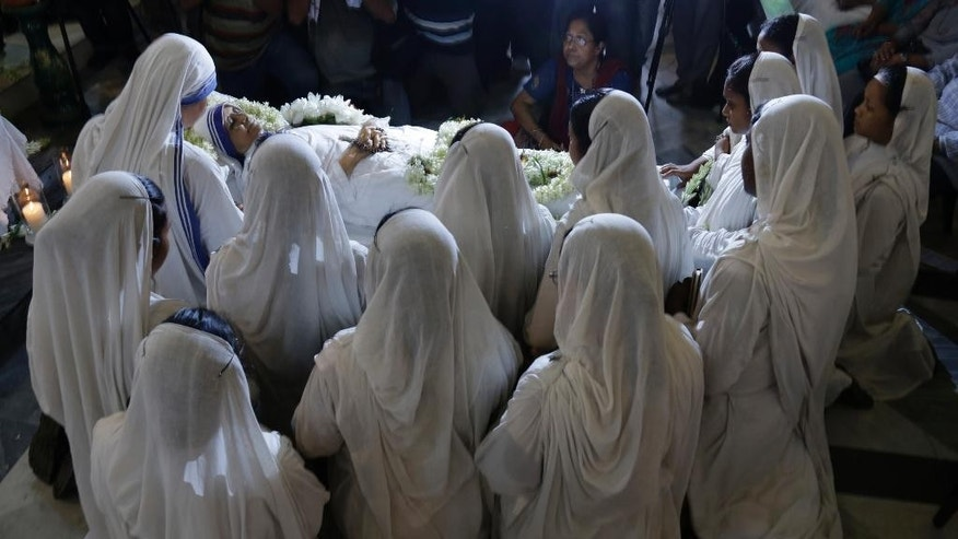 Nuns pray as they surround the body of Sister Nirmala, who succeeded Mother Teresa, as the head of Missionaries of Charity, the order founded by the later in Kolkata, India, Tuesday, June 23, 2015. The 81 years old nun died in Kolkata early Tuesday. (AP Photo/ Bikas Das)