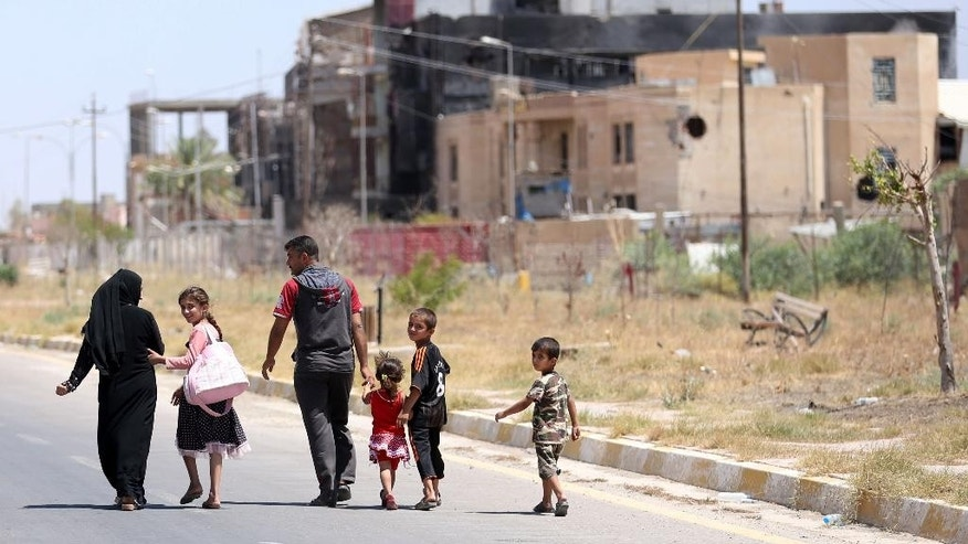In this Sunday, June 21, 2015 photo, a displaced family walks towards their home in Tikrit, 80 miles (130 kilometers) north of Baghdad, Iraq. Civilians are trickling back into Saddam Hussein's hometown as they look to start anew, the consequences of a year under Islamic State rule conspicuously written on its charred buildings and damaged homes.(AP Photo/ Hadi Mizban)