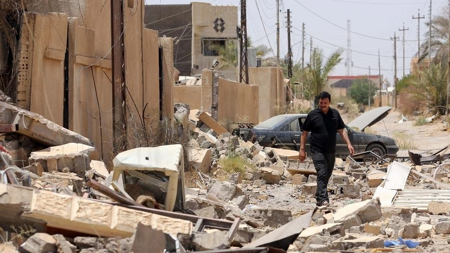 In this Sunday, June 21, 2015 photo, an Iraqi man walks through rubble after returning to his destroyed home in Tikrit, 80 miles (130 kilometers) north of Baghdad, Iraq. Civilians are trickling back into Saddam Hussein's hometown as they look to start anew _ the consequences of a year under Islamic State rule conspicuously written on its charred buildings and damaged homes.(AP Photo/ Hadi Mizban)
