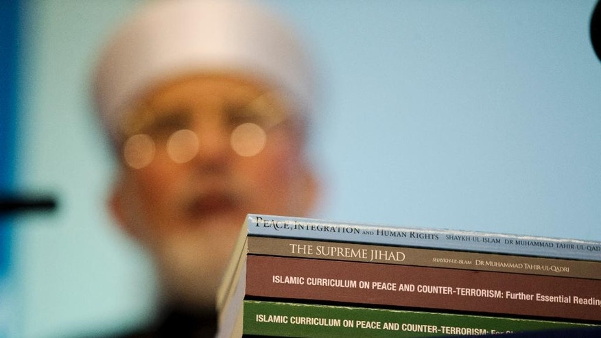 Copies of books he's authored stand stacked on a table as Pakistan cleric Shaykh-ul-islam Dr Muhammad Tahir-ul-Qadri, the founder of  the Minhaj-ul-Quran International organization, takes questions after delivering a keynote speech at the launch of the Islamic Curriculum on Peace and Counter Terrorism in London, Tuesday, June 23, 2015. The curriculum is described by the organizers of the event as a syllabus that provides material to form the basis of educational programs and campaigns against religious extremism and radicalization, and for the promotion of peace. (AP Photo/Matt Dunham)
