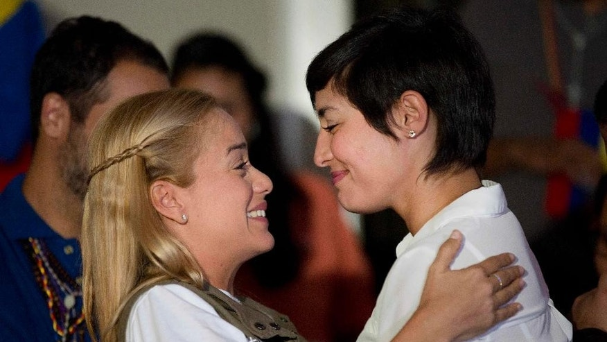 Lilian Tintori, wife of jailed opposition leader Leopoldo Lopez, left, embraces Patricia Ceballos, the wife of jailed opposition San Cristobal Mayor Manuel Ceballos, during a press conference in Caracas, Venezuela, Tuesday, June 23, 2015. Tintori read a letter from her jailed husband at the press conference in which the activist announced his decision to end a 30-day hunger strike after authorities set a date, Dec. 6, for legislative elections. (AP Photo/Ariana Cubillos)
