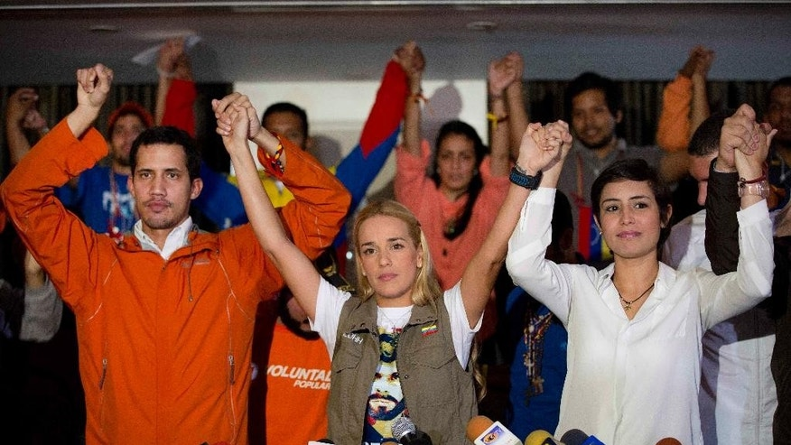 Lilian Tintori, wife of jailed opposition leader Leopoldo Lopez, center, holds up her hands with Patricia Ceballos, wife of jailed opposition San Cristobal Mayor Manuel Ceballos, right, and an opposition member who was on hunger strike, during a press conference in Caracas, Venezuela, Tuesday, June 23, 2015. Tintori read a letter from Lopez at the press conference in which the activist announced his decision to end a 30-day hunger strike after authorities set a date, Dec. 6, for legislative elections. (AP Photo/Ariana Cubillos)