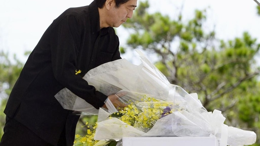 Japanese Prime Minister Shinzo Abe lays a bouquet of flowers during a memorial service at Peace Memorial Park in Itoman on Okinawa islands, Japan, Tuesday, June 23, 2015. Abe attended the ceremony to mark the 70th anniversary of the Battle of Okinawa, one of the bloodiest conflicts of World War II. (Hiroko Harima/Kyodo News via AP) JAPAN OUT, MANDATORY CREDIT