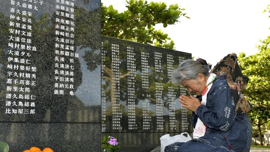 An elderly woman prays in front of the Cornerstone of Peace, monument walls on which the names of all those who lost their lives, at Peace Memorial Park in Itoman on Okinawa islands, southern Japan, Tuesday, June 23, 2015. About 5,000 people held a memorial service Tuesday to mark the 70th anniversary of the Battle of Okinawa, one of the bloodiest conflicts of World War II. (Hiroko Harima/Kyodo News via AP) JAPAN OUT, MANDATORY CREDIT