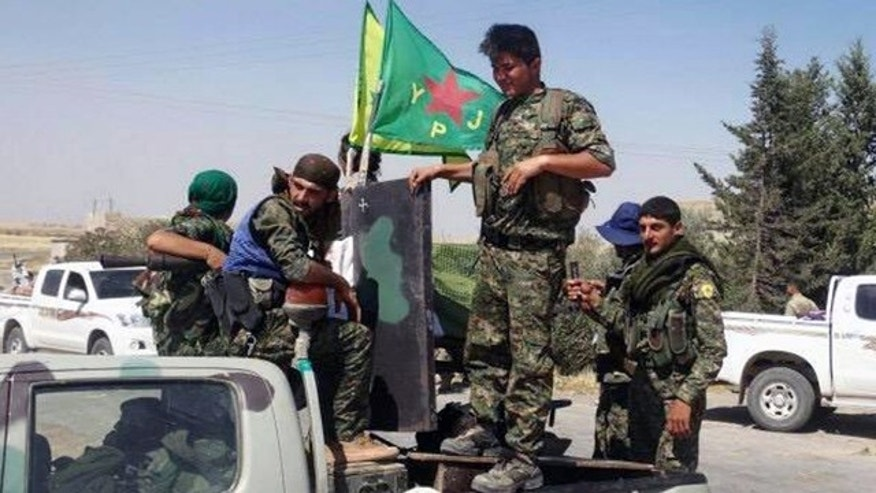 June 23, 2015: In this photo provided by the Kurdish fighters of the People's Protection Units (YPG), which has been authenticated based on its contents and other AP reporting, Kurdish fighters of the YPG sit on their pickup in the town of Ein Eissa, north of Raqqa city, Syria. (The Kurdish fighters of the People's Protection Units via AP)
