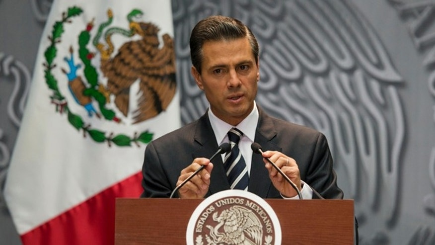 President Enrique Pena Nieto adjusts his microphones as he arrives at a press conference to express his outrage over the recent disappearance of 43 students in Guerrero State following a violent confrontation with the police, in Mexico City, Monday, Oct. 6, 2014. Guerrero state officials worked Monday to determine whether 28 bodies found in a clandestine grave are students who were attacked by police suspected of drug gang links in the southern state of Guerrero. (AP Photo/Rebecca Blackwell)