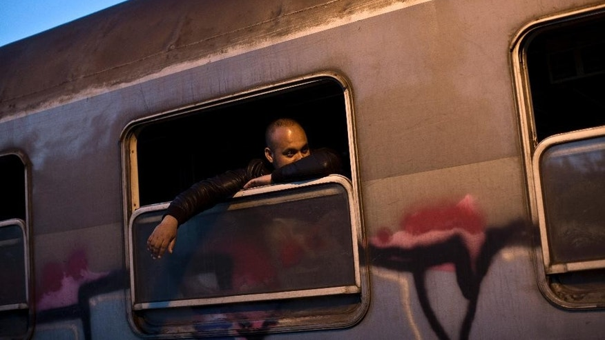 In this photo taken on Monday, June 22, 2015, a migrant looks out of a window of a passenger train in Presevo, close to the Serbian border with Macedonia, 300 kilometers southeast of Belgrade, Serbia. As Hungary ponders building a 4-meter (13-foot) high fence on its 175-kilometer (109-mile) border with Serbia to keep the migrants away, refugees insist that they have no other choice but to move on. (AP Photo/Marko Drobnjakovic)