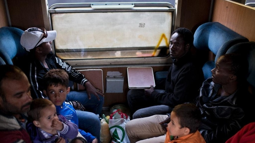 In this photo taken on Monday, June 22, 2015, migrants sit in a compartment of a passenger train in Presevo, close to the Serbian border with Macedonia, 300 kilometers southeast of Belgrade, Serbia. As Hungary ponders building a 4-meter (13-foot) high fence on its 175-kilometer (109-mile) border with Serbia to keep the migrants away, refugees insist that they have no other choice but to move on. (AP Photo/Marko Drobnjakovic)