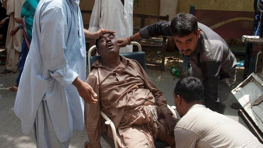 People rush a patient to a hospital suffering from heatstroke in Karachi, Pakistan, Tuesday, June 23, 2015. A scorching heat wave across southern Pakistan's city of Karachi has killed more than 400 people, authorities said Tuesday, as morgues overflowed with the dead and overwhelmed hospitals struggled to aid those clinging to life. (AP Photo/Shakil Adil)
