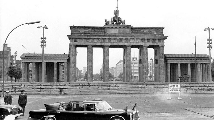 FILE - A May 27, 1965 file photo of Britain's Queen Elizabeth II and Prince Philip being driven in a Mercedes 600 car as they pass the Brandenburg Gate during their first visit to Berlin. The queen is planning to leave Tuesday, June 23, 2015, on a state visit to Germany that will include her first visit to a former concentration camp site. She and her husband Prince Philip plan to visit the Bergen-Belsen camp where diarist Anne Frank and her sister Margot died just weeks before the British liberated it on April 15, 1945. (AP Photo/File)