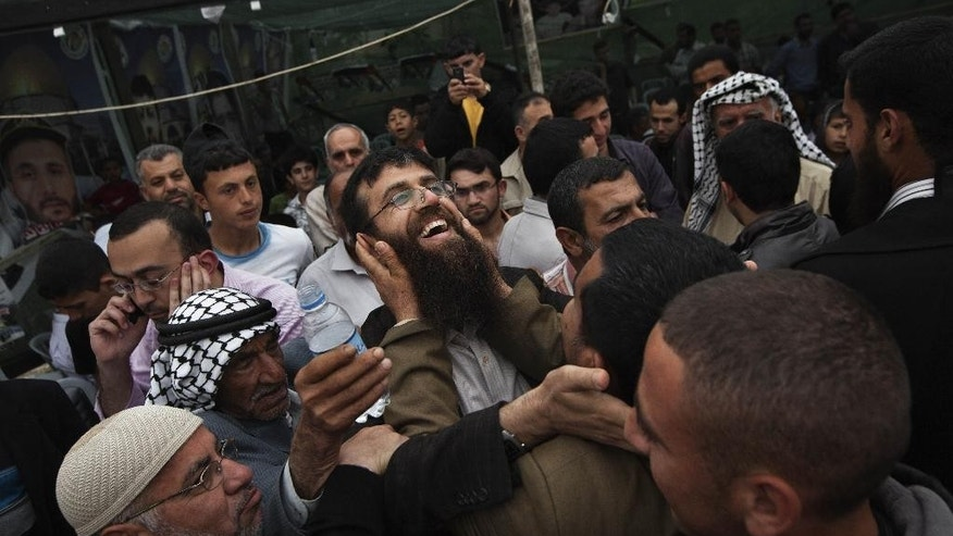 "FILE - In this April 18, 2012 file photo, Palestinian Khader Adnan, center, is greeted by Palestinians during a celebration ceremony after his release from Israeli jails, in the West Bank village of Arrabeh, near Jenin. The International Committee of the Red Cross said Tuesday, June 23, 2015, that Adnan, 36, who has been on a hunger strike for 48 days, faces an ""immediate risk"" of death and urged Israel to allow his family to visit him in line with international conventions. It's the second marathon hunger strike for Adnan who has been held by Israel without charges for almost a year. (AP Photo/Bernat Armangue, File)"