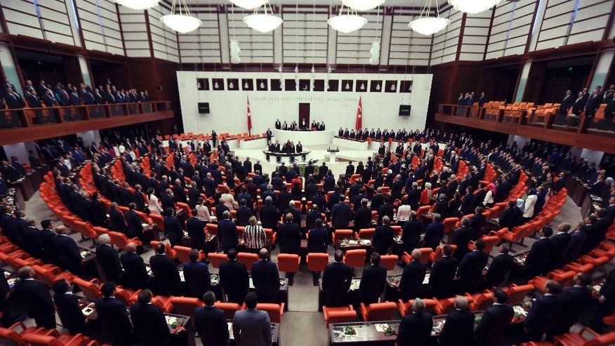 Newly elected legislators stand for national anthem before they take oaths during the Turkish parliament's first session in Ankara, Turkey, on Tuesday, June 23, 2015. The ruling Islamic-rooted Justice and Development Party (AKP) came out first in the June 7 elections but lost its parliamentary majority. (AP Photo/Burhan Ozbilici)