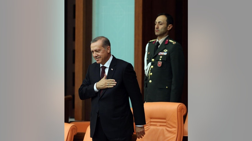 Turkey's President Recep Tayyip Erdogan stands as newly elected legislators take their oaths during the Turkish parliament's first session in Ankara, Turkey, on Tuesday, June 23, 2015. The ruling Islamic-rooted Justice and Development Party (AKP) came out first in the June 7 elections but lost its parliamentary majority. (AP Photo/Burhan Ozbilici)