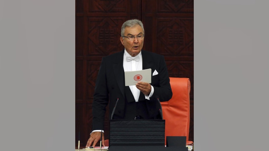Deniz Baykal, eldest lawmaker and former leader of Turkey's social democrats, makes a speech as newly elected legislators take their oaths during the Turkish parliament's first session in Ankara, Turkey, on Tuesday, June 23, 2015. The ruling Islamic-rooted Justice and Development Party (AKP) came out first in the June 7 elections but lost its parliamentary majority. (AP Photo/Burhan Ozbilici)