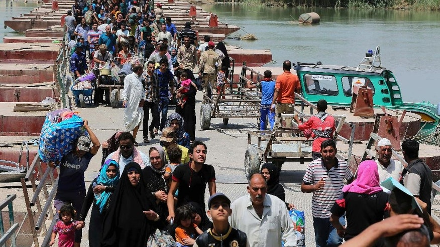 FILE - In this Wednesday, May 20, 2015 file photo, displaced Iraqis from Ramadi, Iraq, cross the Bzebiz bridge, fleeing fighting in Ramadi, 65 kilometers (40 miles), west of Baghdad. The number of people displaced within Iraq due to violence and fighting by the Islamic State group has exceeded 3 million, the United Nations said Tuesday, June 23, a grim milestone for the war-battered country.  (AP Photo/Karim Kadim, File)