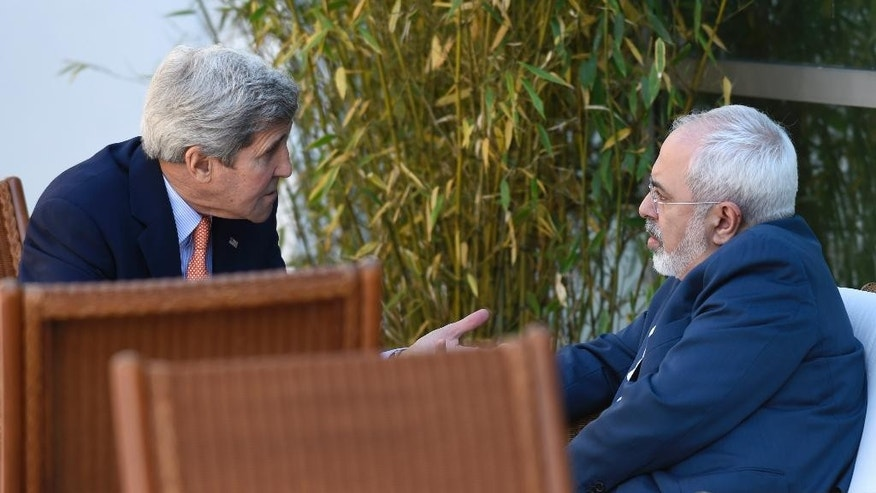 FILE - In this May 30, 2015, file photo, U.S. Secretary of State John Kerry, left, talks with Iranian Foreign Minister Mohammad Javad Zarif, in Geneva, Switzerland during talks on the future of the Iranian nuclear program. The United States and other nations negotiating a nuclear deal with Iran are ready to offer high-tech reactors and other state of the art equipment to Tehran if it agrees to crimp programs that can make atomic arms, according to a confidential document obtained Tuesday, June 22, 2015, by The Associated Press. (AP Photo/Susan Walsh, Pool, File)