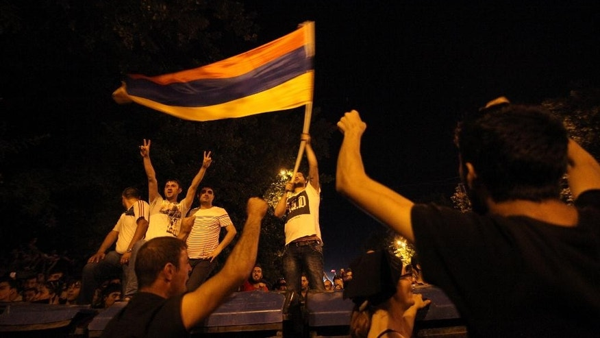 Armenian protesters wave a national flag during a protest rally in the Armenian capital of Yerevan against a hike in electricity prices in the Armenian capital of Yerevan, Tuesday, June 23, 2015. Several thousand demonstrators marched toward the presidential residence in the Armenian capital on Tuesday to protest a hike in electricity prices, renewing their demonstration in even greater numbers after riot police used water cannons to forcefully disperse them earlier in the day. (Hrant Khachatryan/PAN Photo via AP)