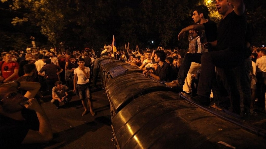 Armenian protesters shout anti-government slogans as they stand on top of barricades during a protest rally in the Armenian capital of Yerevan against a hike in electricity prices in the Armenian capital of Yerevan, Tuesday, June 23, 2015. Several thousand demonstrators marched toward the presidential residence in the Armenian capital on Tuesday to protest a hike in electricity prices, renewing their demonstration in even greater numbers after riot police used water cannons to forcefully disperse them earlier in the day. (Hrant Khachatryan/PAN Photo via AP)