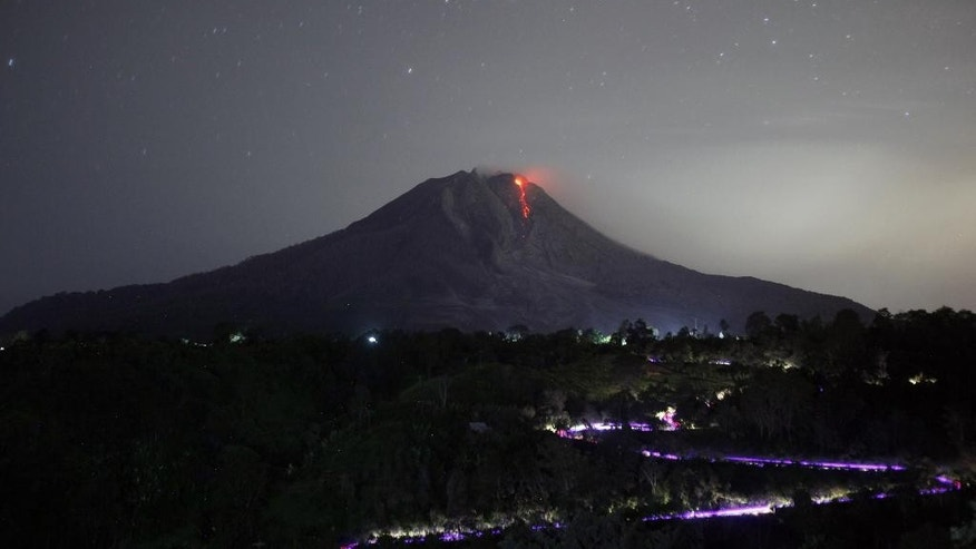 In this photo taken with long exposure, hot molten lava flows from the crater of Mount Sinabung as seen from Tiga Pancur, early Wednesday, June 24, 2015. The volcano has been put at its highest alert level since June 2 following significant increase in its activity. (AP Photo/Binsar Bakkara)