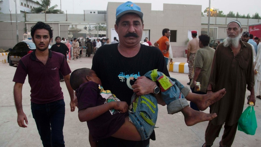 June 23, 2015: A Pakistani man rushes a child suffering from heatstroke to a hospital in Karachi, Pakistan.