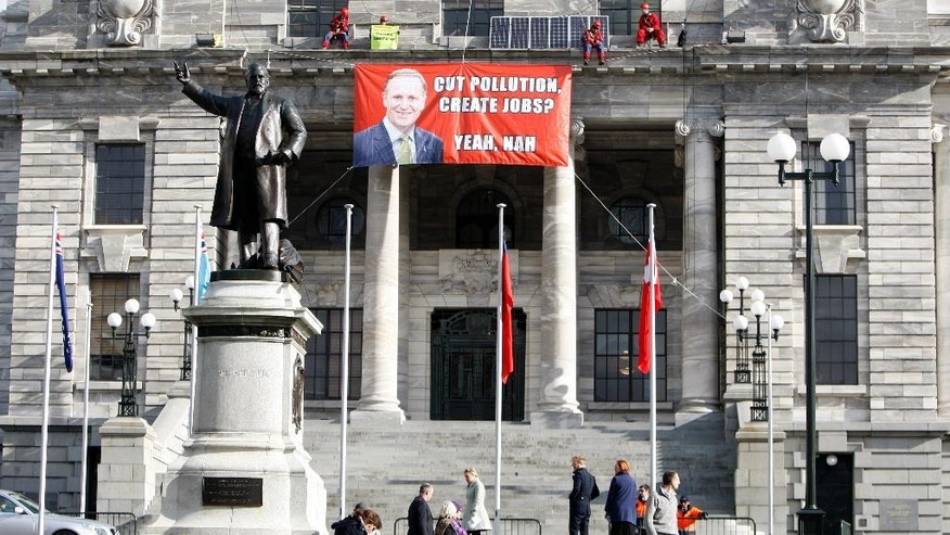 Four Greenpeace environmental protesters perch themselves on a ledge above the main entrance of parliament buildings in Wellington, New Zealand, Thursday, June 25, 2015. The protesters said they were highlighting the government's lack of action in promoting renewal energy. (AP Photo/Nick Perry)