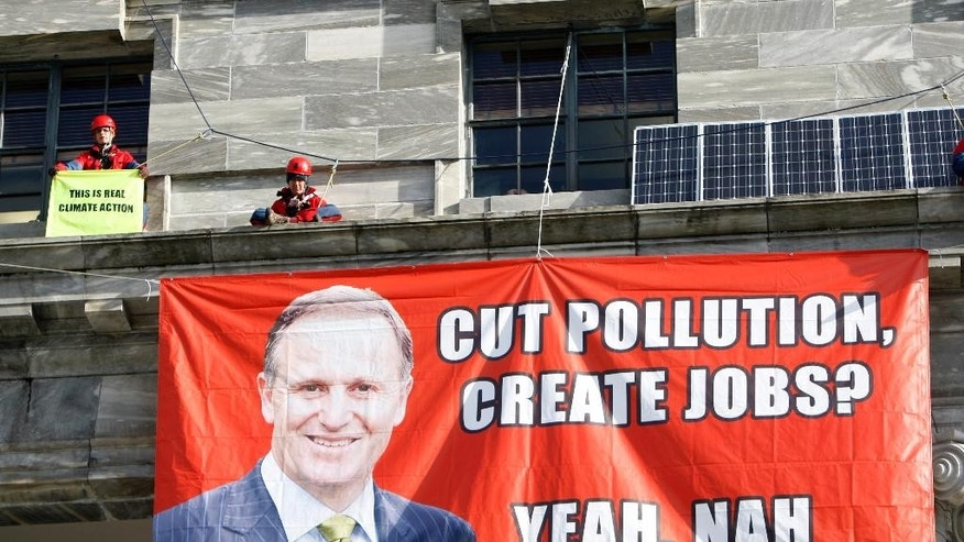 Greenpeace environmental perch themselves on a ledge above the main entrance of parliament buildings in Wellington, New Zealand, Thursday, June 25, 2015. The protesters said they were highlighting the government's lack of action in promoting renewal energy. (AP Photo/Nick Perry)
