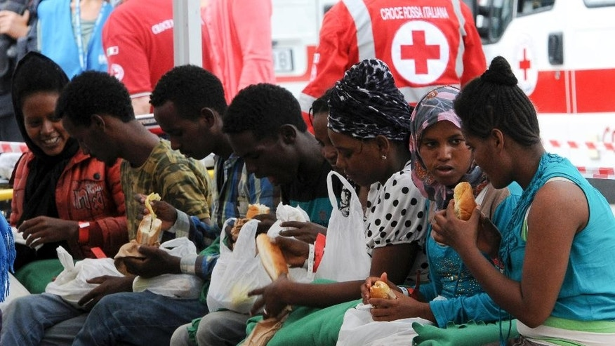 Migrants eat food they received after disembarking from the Norwegian cargo ship Siem Pilot after they were rescued in the Mediterranean Sea, at Palermo harbor, Italy, Wednesday, June 24, 2015. Conflict and poverty have driven more than 100,000 migrants to Europe so far this year, and almost 2,000 have died or gone missing on the perilous sea journey. (AP Photo/Alessandro Fucarini)