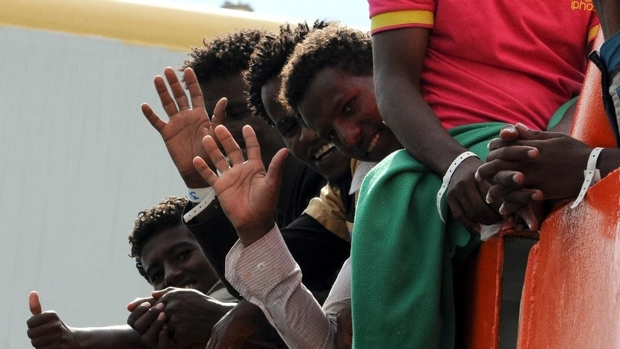 Migrants wave as they wait to disembark from the Norwegian cargo ship Siem Pilot after they were rescued in the Mediterranean Sea, at Palermo harbor, Italy, Wednesday, June 24, 2015. Conflict and poverty have driven more than 100,000 migrants to Europe so far this year, and almost 2,000 have died or gone missing on the perilous sea journey. (AP Photo/Alessandro Fucarini)