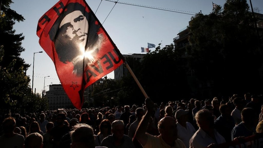 "A pensioner holds a flag bearing the picture of Argentinean revolutionary Ernesto ""Che"" Guevara  during an an anti-austerity protest  in Athens, Tuesday, June 23, 2015. Greece's government defended Tuesday the billions worth of ""harsh"" new budget savings it has offered in talks with creditors, as some of the governing party's own lawmakers spoke out against them. (AP Photo/Petros Giannakouris)"