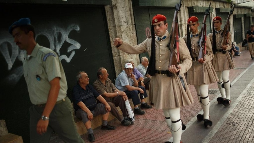"Presidential guards march while some demonstrators sit on the side during an anti-austerity protest in Athens on Tuesday, June 23, 2015. Greece's government defended Tuesday the billions worth of ""harsh"" new budget savings it has offered in talks with creditors, as some of the governing party's own lawmakers spoke out against them. (AP Photo/Daniel Ochoa de Olza)"