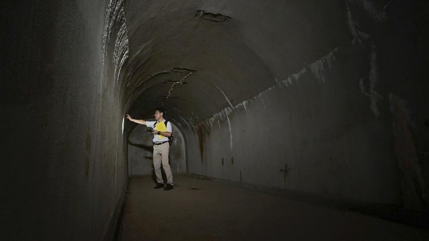 In this Tuesday, June 23, 2015 photo, Takeshi Akuzawa, assistant headmaster of Keio Senior High School, speaks on chief commander's room at underground tunnels that Japan's Imperial Navy once used as secret headquarters underneath of Hiyoshi Campus of Keio University in Yokohama, south of Tokyo. Today, the concrete tunnels sit quietly underneath the high school and university campus, largely untouched and unknown, occasionally visited by guided tours for the students. The school opened them to the media for the first time this week to raise public awareness of the site and the tragic history it represents, in the 70th anniversary year of the end of World War II. (AP Photo/Eugene Hoshiko)