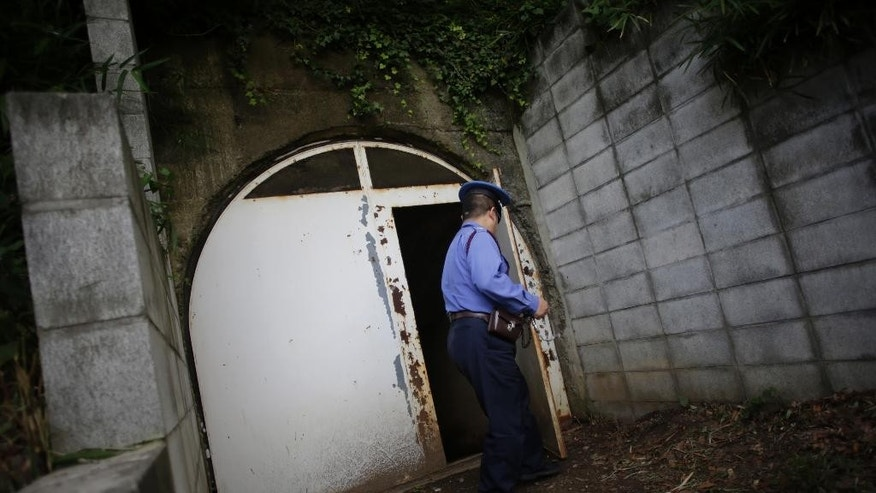 In this Tuesday, June 23, 2015 photo, a security guard closes a metal door of an entrance of underground tunnels that Japan's Imperial Navy once used as secret headquarters underneath of Hiyoshi Campus of Keio University in Yokohama, south of Tokyo. Today, the concrete tunnels sit quietly underneath the high school and university campus, largely untouched and unknown, occasionally visited by guided tours for the students. The school opened them to the media for the first time this week to raise public awareness of the site and the tragic history it represents, in the 70th anniversary year of the end of World War II. (AP Photo/Eugene Hoshiko)