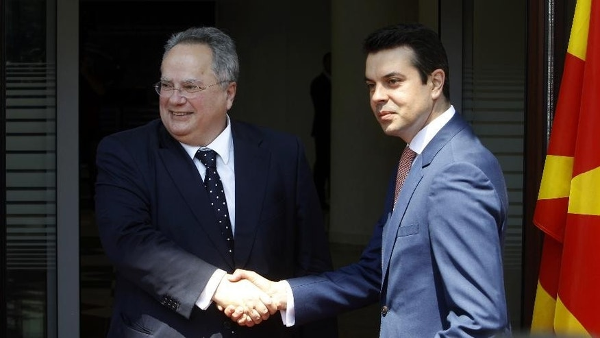 Greek Foreign Minister Nikos Kotzias, left, shakes hands with his Macedonian counterpart Nikola Poposki while posing for the cameras upon his arrival at the Foreign Ministry building in Skopje, Macedonia, on Wednesday, June 24, 2015. Minister Kotzias will meet Macedonian top officials during his visit to Skopje, as a part of his regional trip which included Belgrade and Podgorica. (AP Photo/Boris Grdanoski)