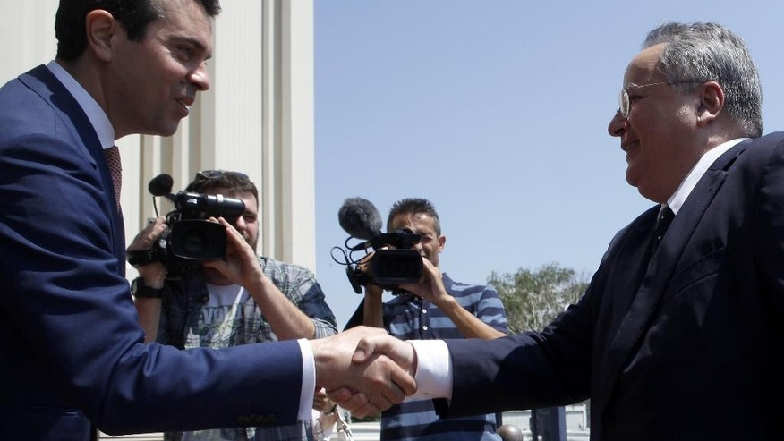 Greek Foreign Minister Nikos Kotzias, right, is welcomed by his Macedonian counterpart Nikola Poposki upon his arrival at the Foreign Ministry building in Skopje, Macedonia, on Wednesday, June 24, 2015. Minister Kotzias will meet Macedonian top officials during his visit to Skopje, as a part of his regional trip which included Belgrade and Podgorica. (AP Photo/Boris Grdanoski)